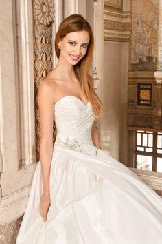 Demetrios 3212, collectie 2015 Een zeer stijlvolle trouwjurk met sweetheart decolleté en halterkraag en een prachtig vallende sleep. De applicatie in de taille en de asymmetrische vormgeving staan centraal bij deze jurk. Koonings kan de jurk ook strapless maken.