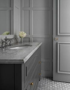 Chic monochromatic gray bathroom boasts a dark gray washstand placed on gray marble hex floor tiles and fitted with brass knobs and a gray marble countertop holding an oval sink with a polished nickel hook and pout faucet beneath an inset vanity mirror.