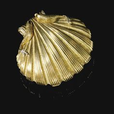 GOLD AND DIAMOND COMPACT, 'DELFINI', ALOISIA RUCELLAI Designed as a gold scallop shell, the front embellished with four sculpted fish, accented with circular- and single-cut diamonds, opening to reveal a powder compartment fitted with a mirror, signed Aloisia.