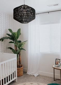 neutral modern baby boy nursery with a bohemian boho vibe, greenery, wallpaper and pops of wood accents baby room nursery
