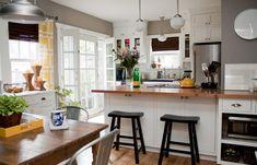 Breakfast bar overlooking kitchen, glass cabinets, wooden countertop + stainless steel fridge