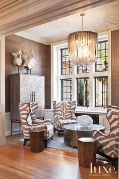 Zebra-print wing chairs with classic nailhead trim is complimented by the glitzy, graceful chandelier that drapes over the reading alcove. A happy marriage of texture and pattern enlivens the silvery, subdued color palette and exudes an organic-glam vibe.