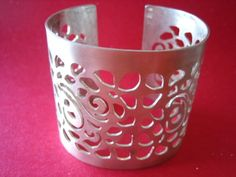 A beautifully floral cut out cuff in Sterling Silver. It is 50mm (2) wide. Satin finish.    This cuff has been sawpierced (hand cut outs with a