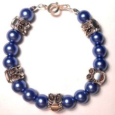Handmade Jewellery - Bracelet £1.50. A gift idea by Sarah Mckenzie found on www.MyOwnCreation.co.uk: Beaded bracelet with blue pearl effect 8mm beads and Tibetan silver owls.  On clear elasticated cord with silver clasp fastening.