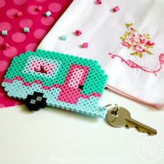If you've got an old school camper or dream of hitting the road with one someday, embrace the adventure with a super-cute retro camper Perler bead keychain!