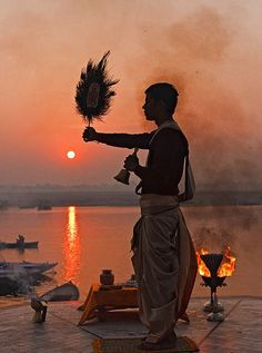 Travel Inspiration for India - Sunrise Hindu ceremony called the Aarti or waving of Divaas on the banks of River Ganga, India.