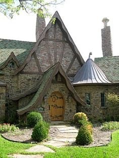 Storybook Cottage with steeply  pitched roofline punctuated by  a profusion of dormers, gables, elaborate chimneys & decorative ornamentation.