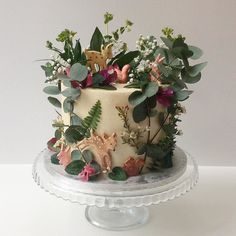 Enchanted forest layer cake with hand animal illustrations by our girl @harrietrosedraws piped in white chocolate & dusted in edible lustre.