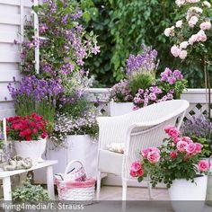 Korbstuhl und Beistelltisch inmitten blühender Pflanzen auf dem Balkon