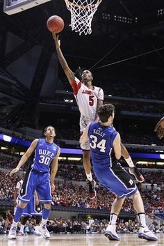 Louisville guard Kevin Ware goes up for a shot against Duke forward Ryan Kelly during the first half of the Midwest Regional final in the NCAA college basketball tournament, Sunday, March in Indianapolis. At left is Duke guard Seth Curry Louisville Basketball, University Of Louisville, Duke Basketball, College Basketball, Ncaa College, Seth Curry, Ryan Kelly, Duke Blue Devils, Louisville Cardinals