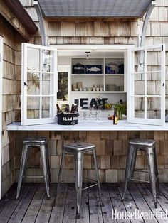 "Home > Decorating & Ideas > Home Tours > A Chic California Beach.  ""The honed Calacatta marble counter in the kitchen extends outside to make passing food easier. Tolix Marais stools from Design Within Reach are pulled up to the counter...Why let size cramp your style? Twelve can sleep comfortably in this dreamy 1,650-square-foot weekend house in coastal Marin County, California."""