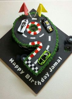 Formula 1 racing car track number nine cake with toy cars for the hirthday boy to play with afterwards. From Out Of This World Cakes in Bristol Plus
