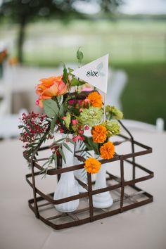 vintage milk bottle carrier with small floral arrangements and table numbers #tabledecor #weddingreception #weddingchicks http://www.weddingchicks.com/2014/01/24/true-love-texas-wedding