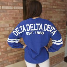 Feel like royalty wearing this new royal blue Spirit Football Jersey. Over-sized v-neck resort tee with white classic greek letters on the front and Delta Delta Delta on the back. Sleeves feature two white screen printed stripes.