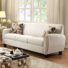 room with overstuffed beige sofa beige linen armchairs and a tufted ...