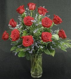Red Romance-   A dozen beautiful long stemmed red roses arranged in a clear glass vase with assorted foliages and accents.