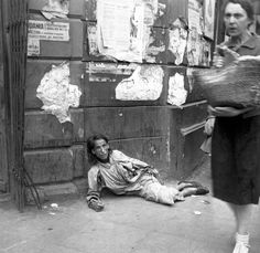 A starving, homeless Polish Jewish woman sits on the pavement while interned in the Warsaw Ghetto. September 19, 1941.