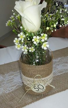 Mason jars with burlap !!! Love the touch with the flowers !!! Perfect for a country wedding !!! AUNT & Uncle 50th wedding anniversary party !