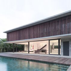 Strips of recycled hardwood enclose a narrow balcony that runs around the edge of this family house on the outskirts of a fishing village in Thailand