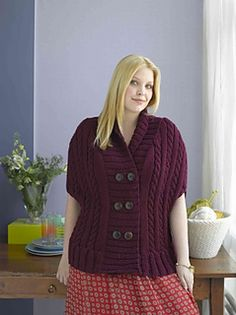Sizes S-L, 1X-2X. This buttoned cape features a classic cabled design. (Lion Brand Yarn)