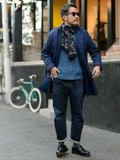 インディゴブルーのステンカラーコートを主役にネイビー、青系のニット、パンツでまとめたコーデ