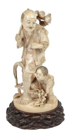 An Ivory Okimono of a Farmer , he stands holding a branch of kumquat over his shoulder while his son picks berries at his feet, brown etched details, inlaid red lacquer signature panel beneath, height 18.4cms, Meiji-Taisho Era; with wood stand