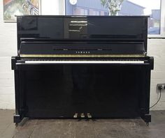 A 1988, Yamaha MC10Bl upright piano with a black case and polyester finish at Besbrode Pianos £4500. Piano has an eighty-eight note keyboard and three pedals.