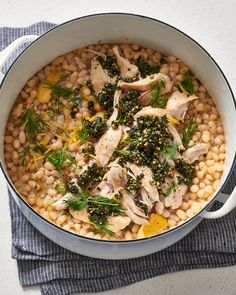 A recipe for slow-cooked white beans and chicken thighs in a lemon and herb broth, which can be prepared in the oven or slow cooker.