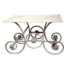French Marble Topped Pastry Table  France  19th Century  This lovely antique French pastry table has a marble top with a painted iron base. The legs are large c-scrolls on either side connected with round rods and central flower finials.