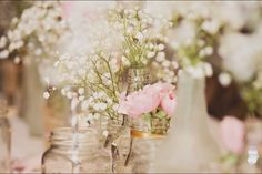 Babies breath and garden roses in vintage bottles