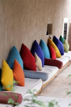 Colourful pillows line re-purposed pallet benches while bolsters act as armrests.