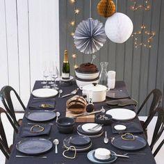 Une table de réveillon noire et chic. ccessoirisée de vaisselle en céramique ultra tendance, de ronds de serviettes délicatement cuivrés, la table de réveillon noire devient éclatante et résolument élégante.
