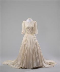 This wedding dress was made from Second World War parachute silk and was worn by bride Carol Thomas (nee Gifford) when she married Owen Thomas after he was discharged from the New Zealand Army in 1946.At this time, fabric for new clothing (particularly silk) was still scarce. Parachute silk was highly sought after but rare, as nylon had replaced silk in 1942.  Using parachute silk was also a way for the bride to honour the war service of her husband-to-be.