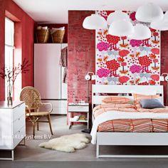 Rote Wände, orangefarbene Bettwäsche, rosarote Blumenmuster: Hier wird mit warmen, lebendigen Farbtönen nicht gespart. Mehr Ideen auf www.roomido.com