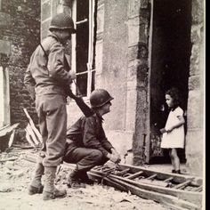 US soldiers talking to the only French girl left in Cerisy-la-salle, France after the Allied invasion of Normandy. July 25, 1944