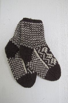Handknitted baby socks with norwegian pattern in brown and beige