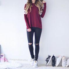 Suéter vinho, calça preta rasgada e tênis branco da Adidas.