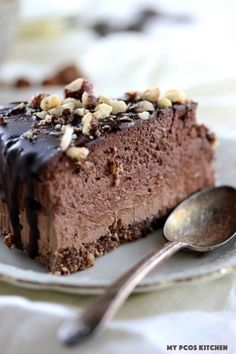 Low Carb Keto Triple Chocolate Cheesecake - My PCOS Kitchen - A closeup shot of a death by chocolate cheesecake slice covered in crushed hazelnuts with a chocolate ganache.