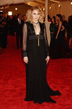 Greta Gerwing de Saint Laurentcon un vestido de mangas transparentes y collar tipo tassel dorado.