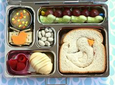 Planetbox lunch with ducky sandwich, hardboiled egg, raspberries, applesauce with little duck candies, duck cucumbers and grapes.