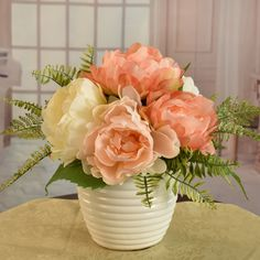 A beautifully hand crafted designer bouquet created peach and cream peonies accented with wispy fern. Placed in a  cream white ceramic vase. Set this design just about anywhere in your home or office.  Great  idea for gifts.  Perfect size for RVs, , side tables and baths. 11'' H x 10'' W x 10'' D