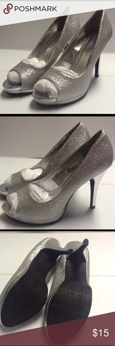 Silver Glittered Peep Toe Pumps New in original box. Made by Rampage with the style name of Gracee. Platform is approx 1 inch with a heel of 4.5 inches. Manmade materials. Please note that the heel on the right shoe has a minor flaw, this is shown in picture number 4. Rampage Shoes Heels