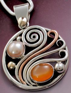 Jima Abbott made this circle wave pendant with pink/orange moonstone and fresh water pearl. Made with silver copper and gold in 2017.