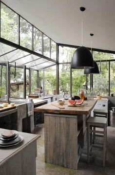 This greenhouse-inspired kitchen features floor-to-ceiling window walls to allow for the maximum amount of natural light