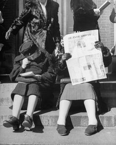 Women reading newspapers while waiting in line for matinee performance of the Boston Symphony Orchestra. Boston, MA, US, 1944.  Photographer:Walter Sanders. LIFE image.
