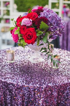 Glamorous wedding ideas: Sparkly purple table cloth with lush red and purple floral arrangement.