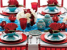 I like the combo of colors and understatement of the theme.  The colorful holiday table setting above is from O, The Oprah Magazine. Blue dishes, ginger jars and a woven table runner play against the red chargers, stemware, napkins and candle holders. Flatware is Ricci's bamboo pattern.
