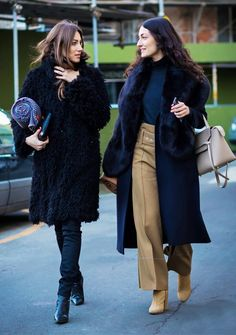 Left, a black textured coat is paired with skinny jeans and black boots. Right, a navy turtleneck, fur-trimmed coat, and khaki trousers are paired with tan boots.