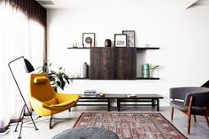 Single yellow midcentury armchair in modern living space with traditional rug and black floor lamp