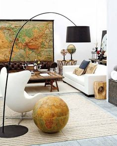 personalized space with white egg chair, white sofa, neutrals of wood & metals + contemporary black floor lamp, map, globe
